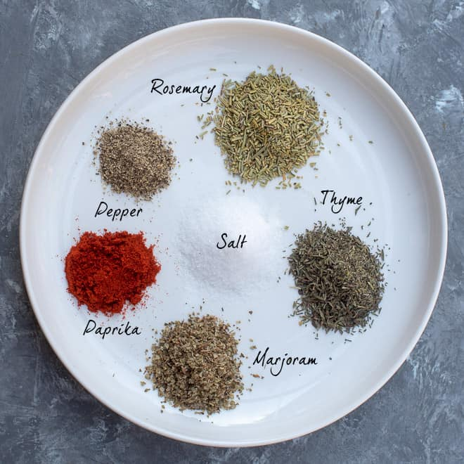The spices in the Beef Stew Spice Mix on a white plate with overlay text.