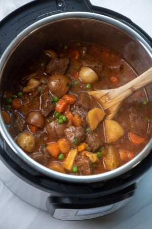 A wooden spoon in an Instant Pot full of Beef Stew.