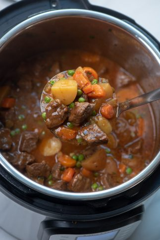 A ladle scoops some beef stew from an Instant Pot.