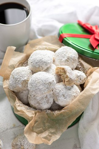 Small round cookies dusted with powdered sugar in a parchment paper lined container.