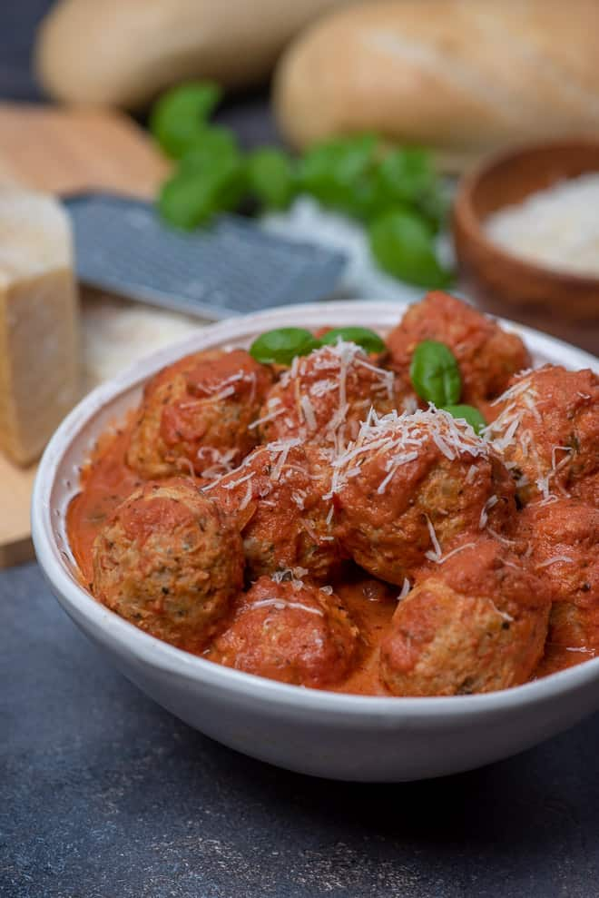 A white serving bowl filled with Slow Cooker Chicken Parmesan Meatballs sprinkled with grated Parmesan.