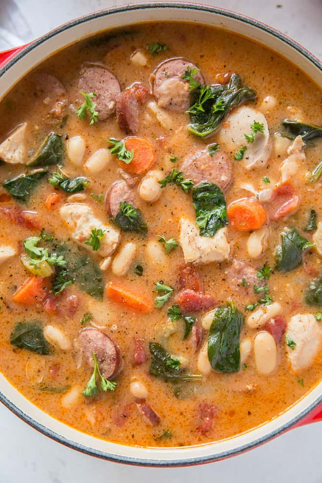 A close up image of Chicken and Sausage Stew with White Beans and Spinach in a Dutch oven.