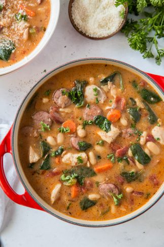 A pot filled with chicken and sausage stew with white beans and spinach.
