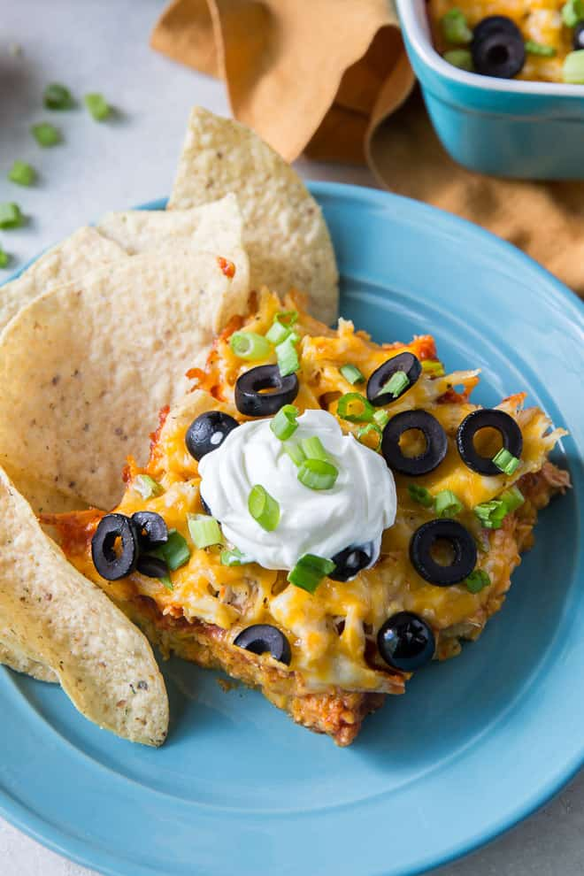 A close up image of the Chicken Tortilla Casserole on a blue plate with tortilla chips.