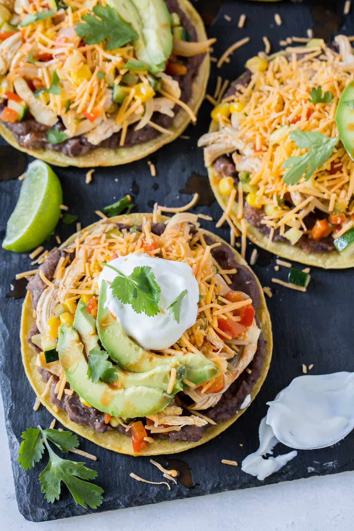 Tostadas topped with cheese, sour cream and avocado.