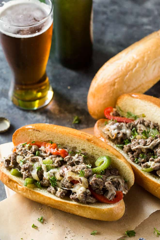 Philly Cheesesteaks with a glass of beer in the background.