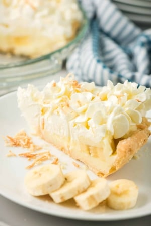 A slice of Banana Cream Pie on a serving plate with sliced bananas.