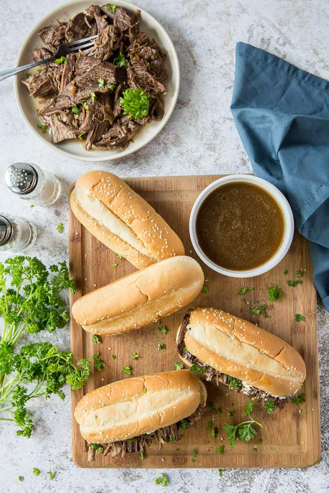 An overhead shot of a cutting board full of sandwiches, a bowl of au jus, and a bowl full of shredded beef.