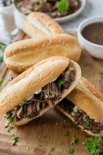 Shredded beef on hoagie rolls stacked on a cutting board.