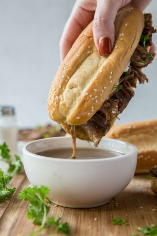 A sandwich being dipped into a small bowl of au jus.