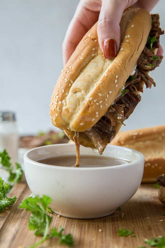 A slow cooker French Dip Sandwich is dipped into a bowl of au jus.