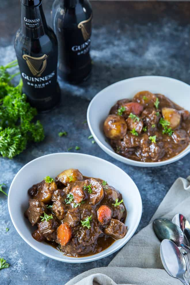Two white serving bowls of Irish Beef Stew with two bottles of Guinness Draught behind them.