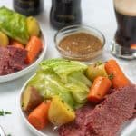 Corned beef, cabbage, potatoes and carrots on a white plate.
