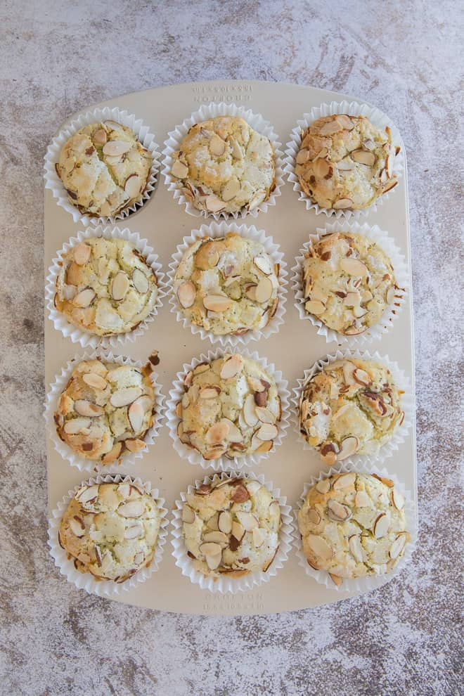 An overhead shot of the muffin pan with the baked Lemon Almond Poppy Seed Muffins just after they've come out of the oven.