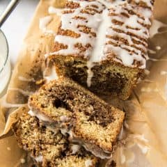 A sliced loaf of Cinnamon Swirl Bread on a sheet of parchment paper.