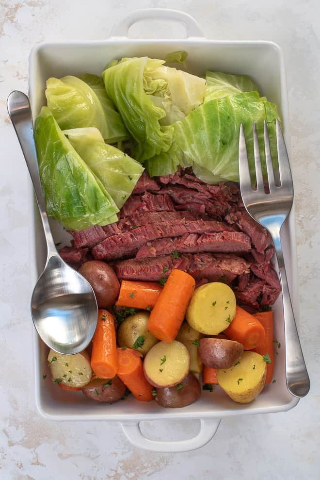 A white serving dish filled with sliced corned beef, cabbage, carrots and potatoes.