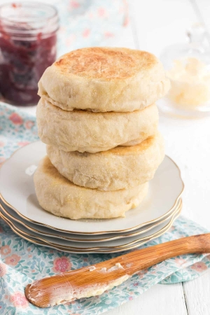 A stack of four English muffins on a plate.