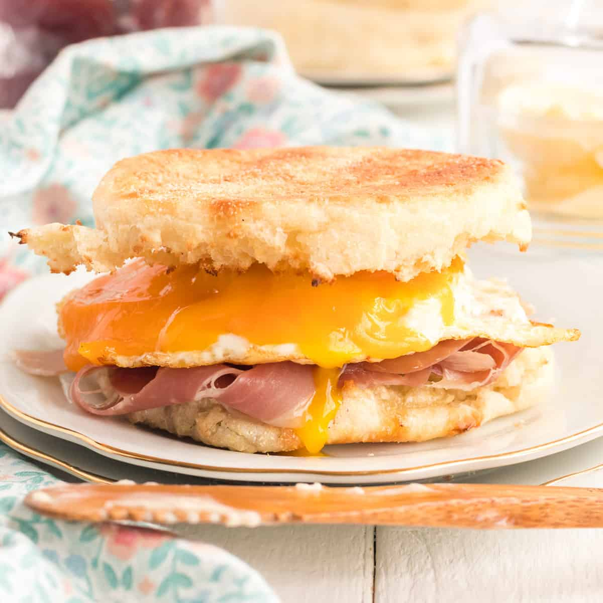 A breakfast sandwich made with egg, ham and cheese on a toasted English muffin.