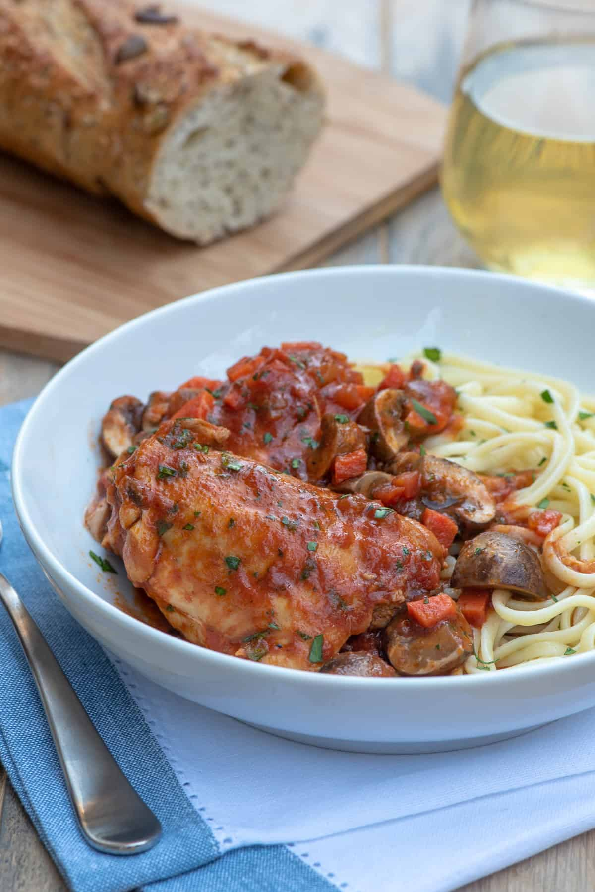 A serving of Slow Cooker Chicken Cacciatore in a white serving dish with pasta.