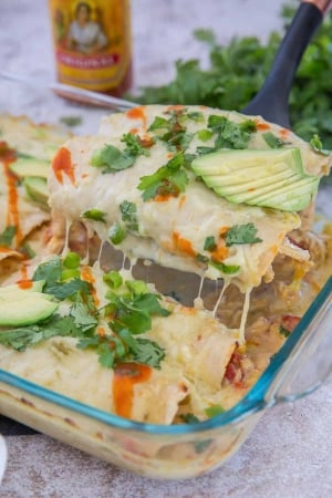 A spatula lifts enchiladas from the dish with hot sauce in the background.
