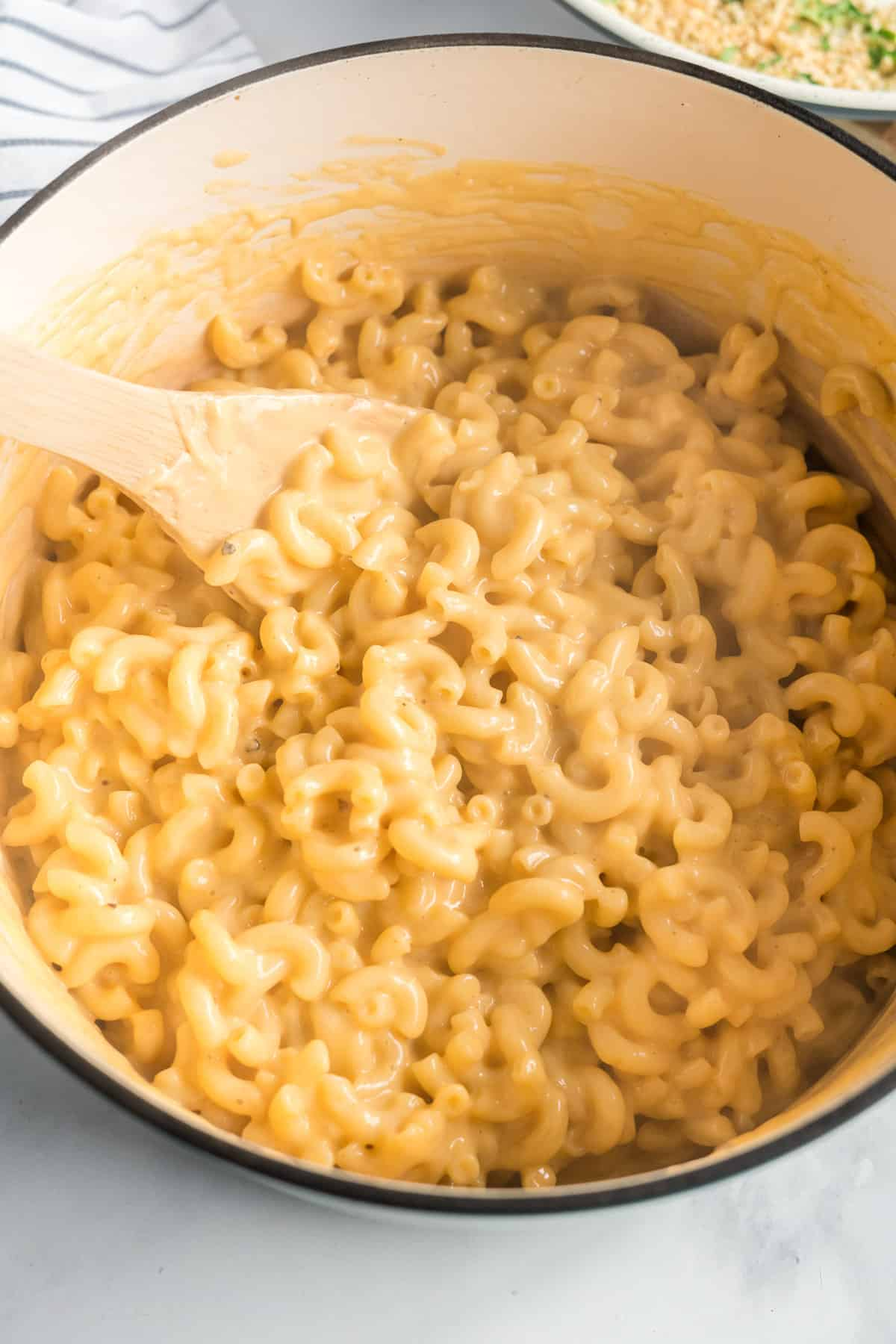 The creamy pasta and cheese mixture after it is combined in the Dutch oven.