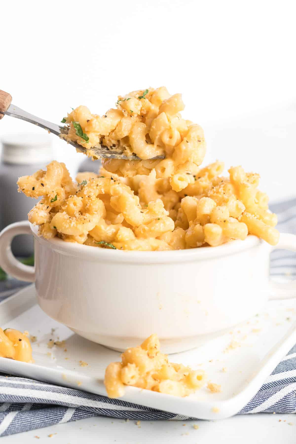 An individual serving of Stovetop Macaroni and Cheese being scooped up with a spoon from a small white bowl.