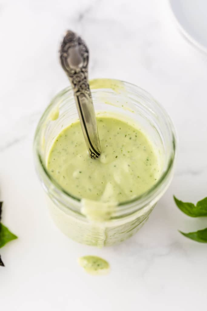 A mason jar full of Basil Buttermilk Dressing shot from the top.