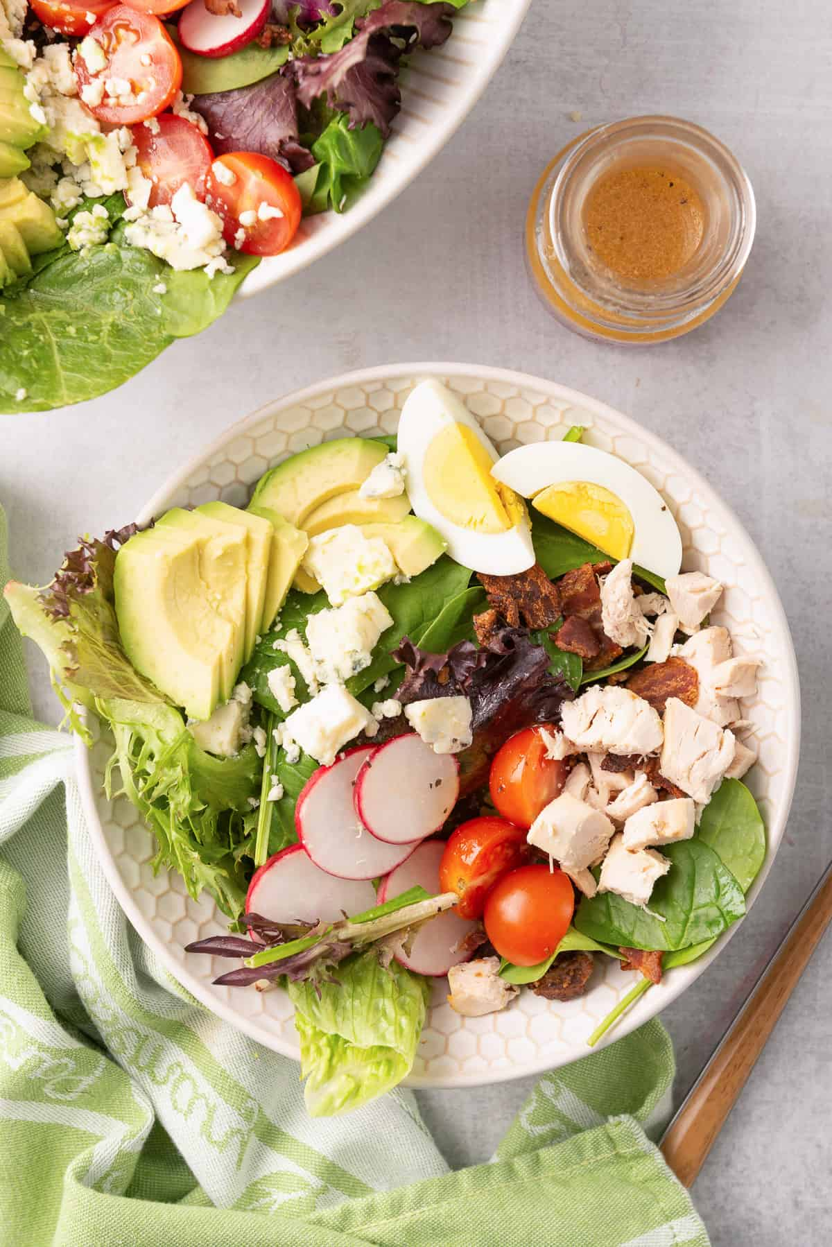 An over the top shot of Chicken Cobb Salad in a white bowl with a green and white cloth.