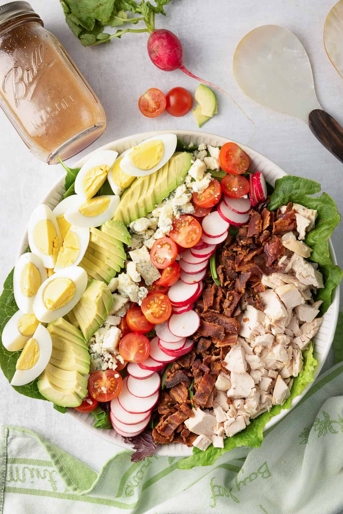 An over the top shot of the Chicken Cobb Salad ingredients lined up in a large white serving bowl.