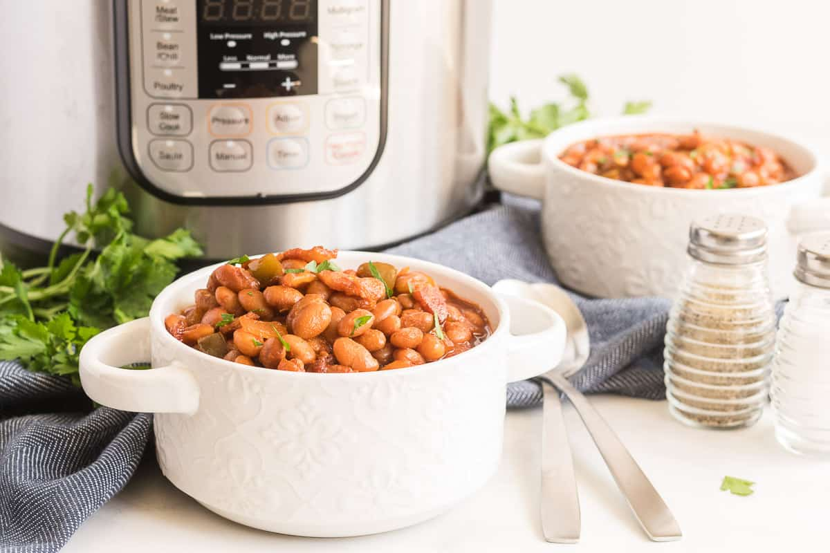 Two white bowls filled with baked beans sit in front of an Instant Pot.