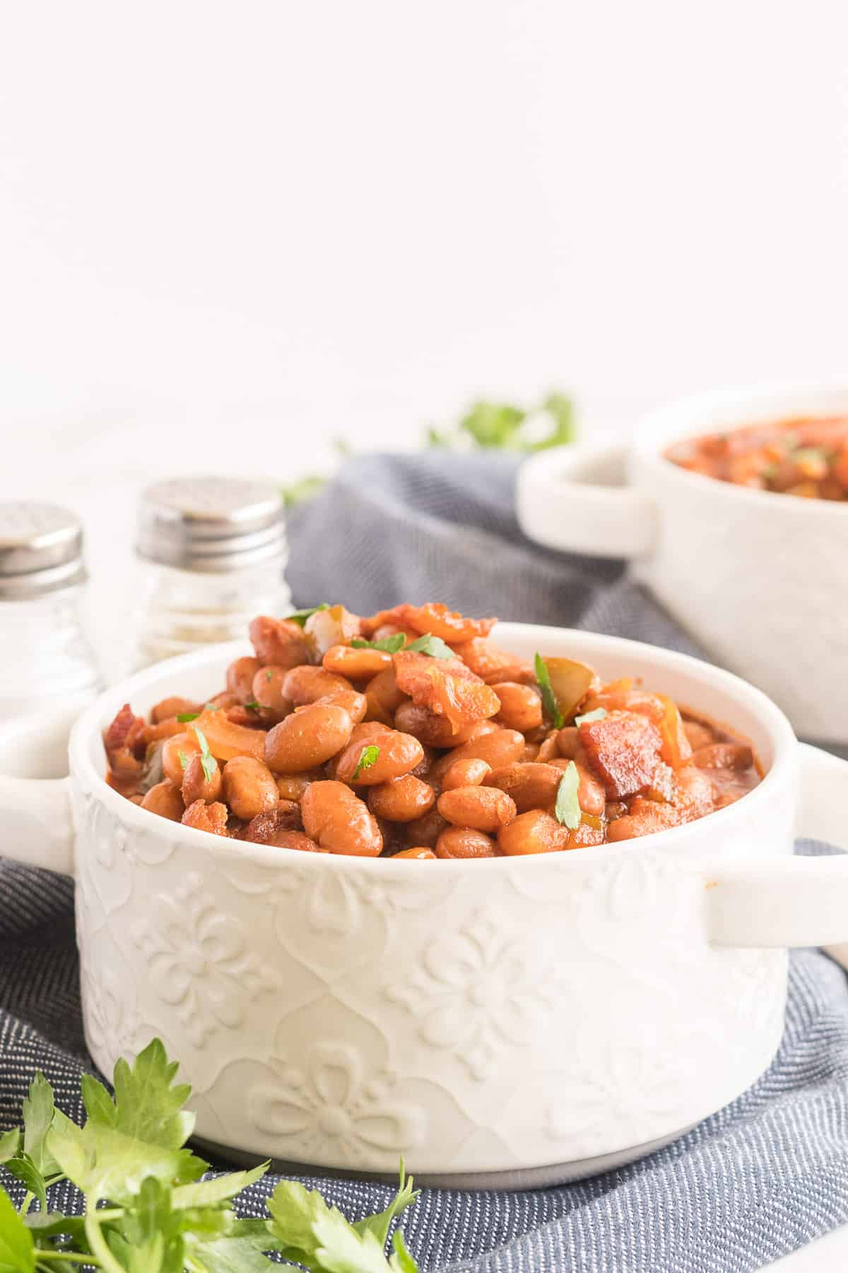 Baked Beans in a white serving dish with a blue cloth underneath.