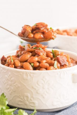 A spoon lifts some baked beans from a white serving dish.