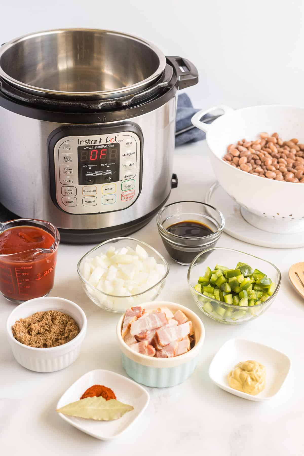 The baked bean ingredients and an Instant Pot on a white surface.