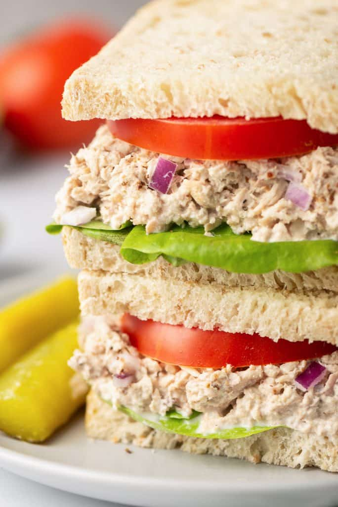 A close up of a Lemon Pepper Tuna Sandwich layered with tomatoes and lettuce on a white plate with pickles.