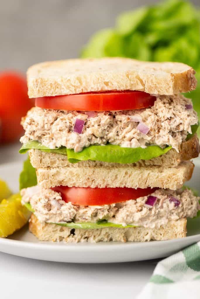 A Lemon Pepper Tuna Sandwich with tomatoes and lettuce is sliced in half and stacked on a white plate.