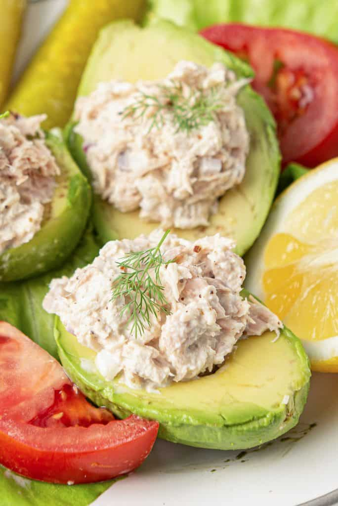 Avocado halves stuffed with Lemon Pepper Tuna on a plate with slices of tomato and lemon.