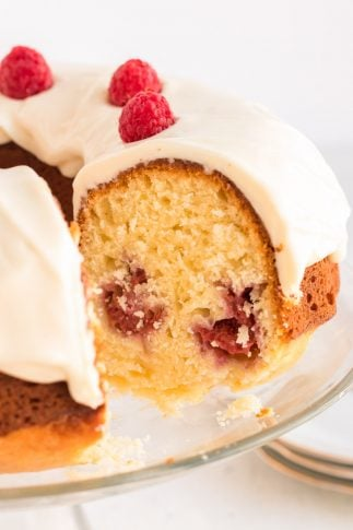 A side view of the Lemon Raspberry Bundt Cake with a slice missing revealing the center.