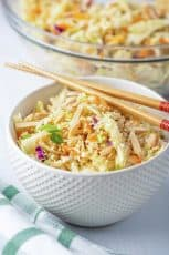 A white bowl filled with Ramen Cabbage Salad with chopsticks lying over the top.