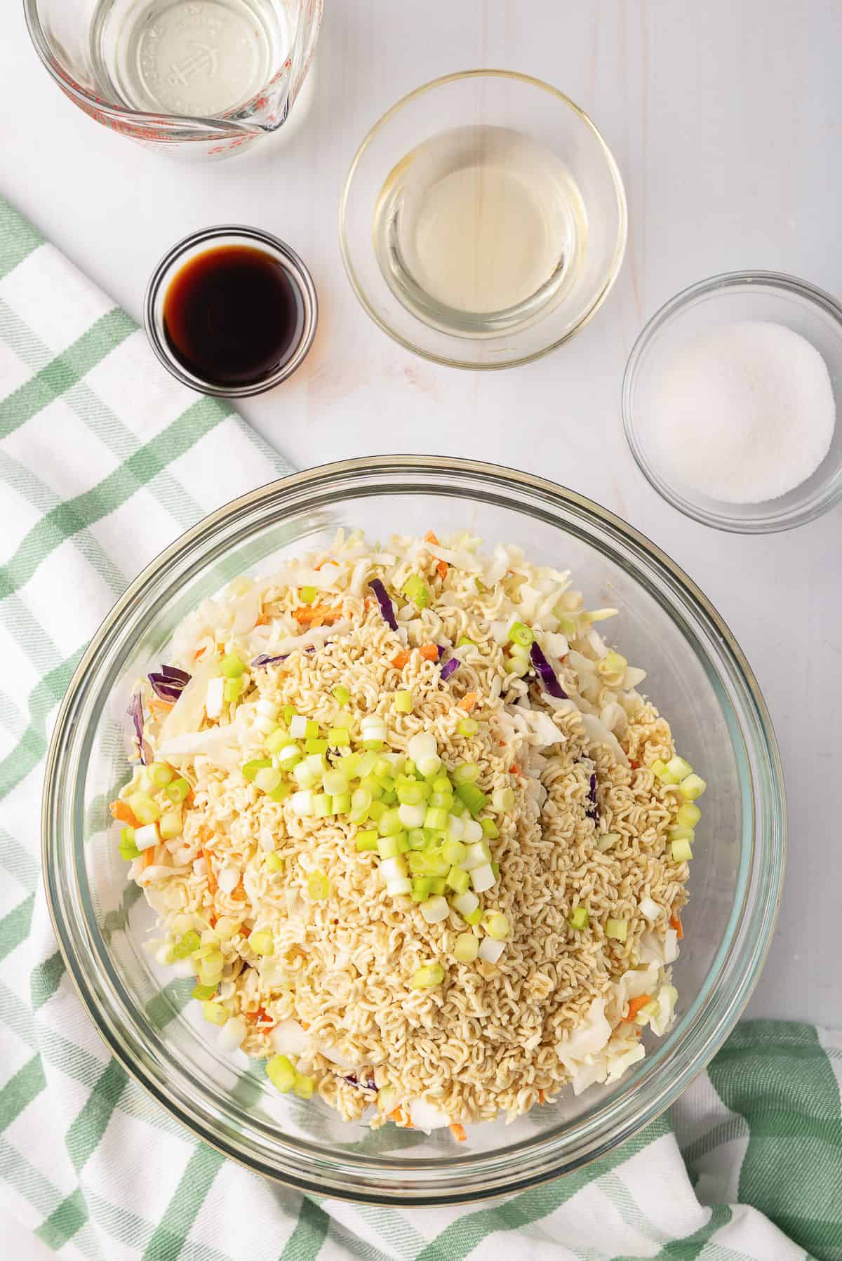 The salad ingredients are combined in a large glass mixing bowl.
