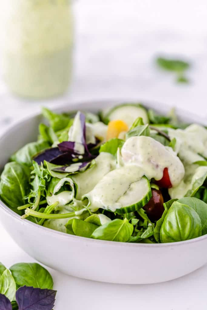 A white bowl filled with green salad