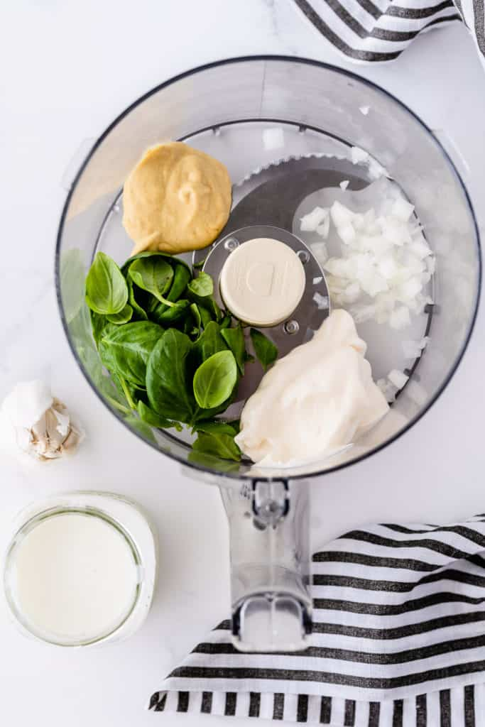 Al the ingredients required to make Basil Buttermilk Dressing in the bowl of a food processor.