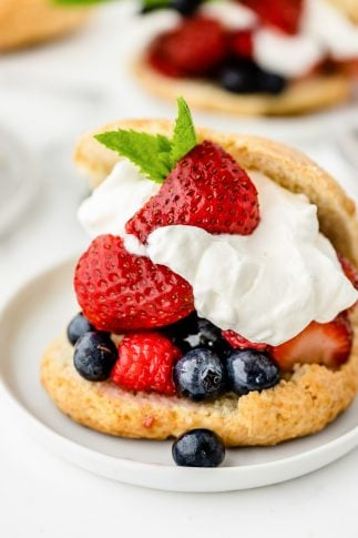 Shortcake stuffed with berries and whipped cream on a white plate.