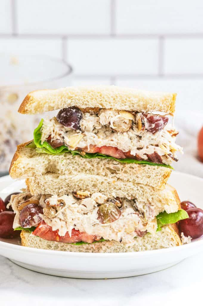 A Napa Almond Chicken Salad Sandwich sliced in half and stacked on a plate with grapes.