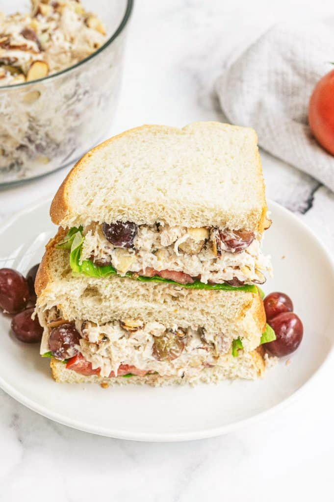 A Panera copycat chicken salad sandwich sliced in half and stacked on a white plate with grapes.