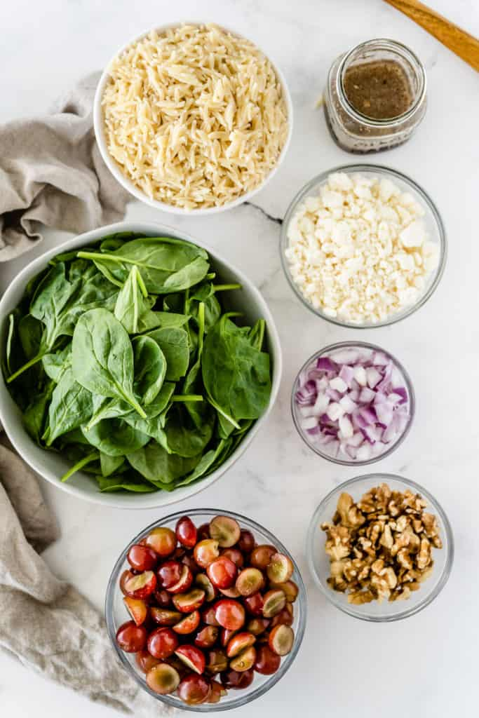 The ingredients to make Orzo Grape Feta Salad on a white surface shot from over the top.