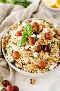 The orzo pasta salad in a white serving bowl with grapes and lemons placed around it.