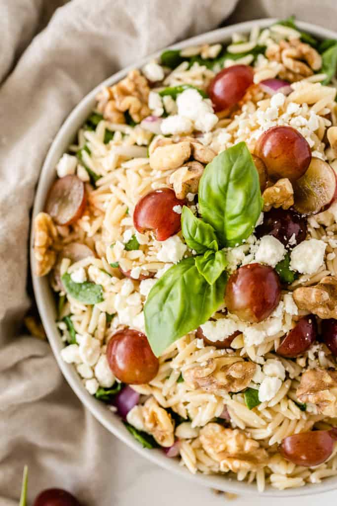 A closeup of Orzo Grape Feta Salad in a white bowl.