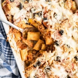 A spoon digs in to the center of the Pizza Pasta in a white casserole dish.