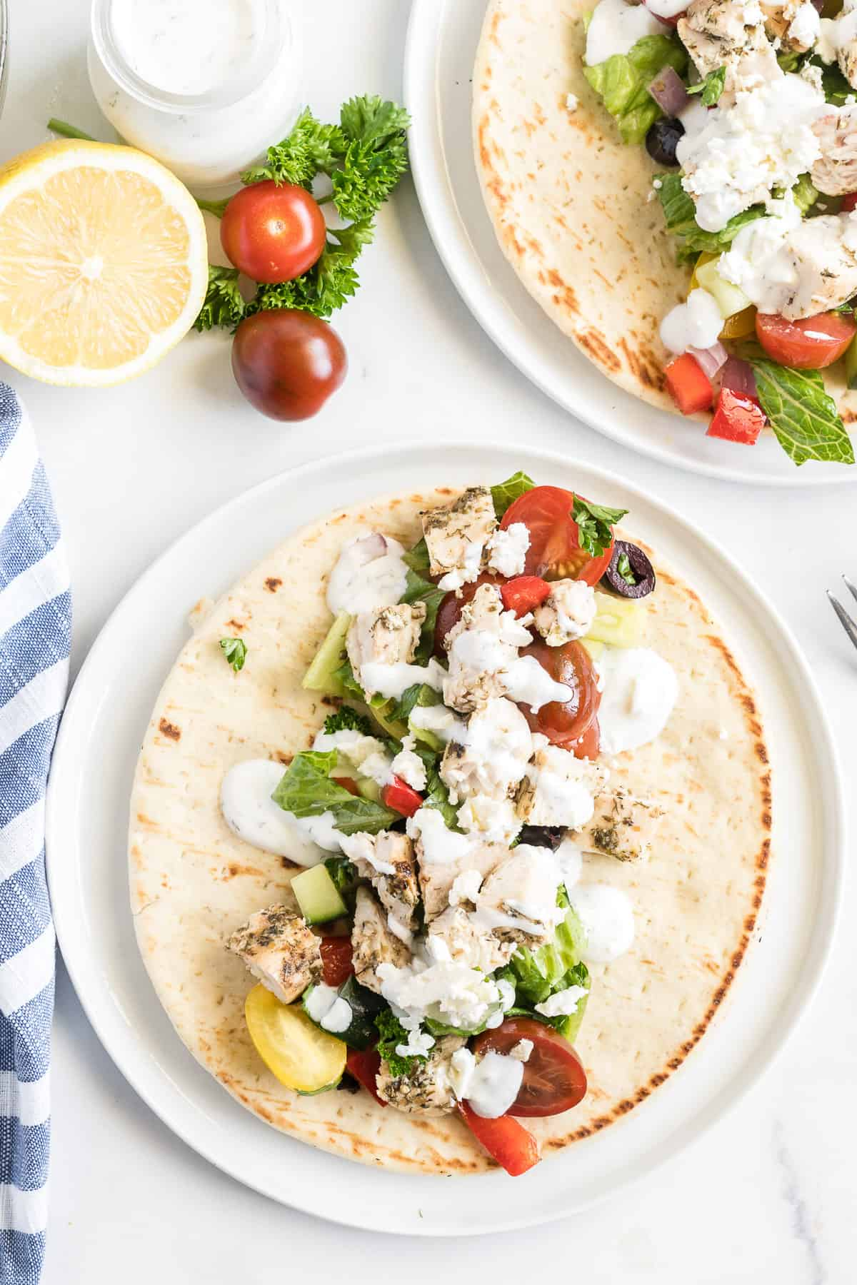 A pita on a plate layered with lettuce, vegetables, and grilled Greek chicken.