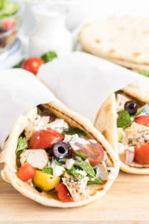 Two pitas stuffed with chicken and greek salad and wrapped in parchment paper.